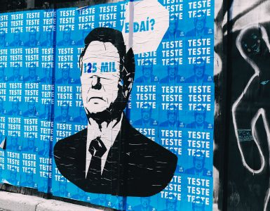 """Streetart of Blindfolded Bolsonaro with the tagline """"125 thousand, so what?"""" and the background """"test, test, test"""""""